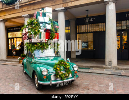 1967 Morris Minor piled high with gifts, as an 'Instagram moment' outside the South Plaza of Covent Garden in central London, England, UK - Stock Image