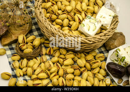 Pistachio and nougat in a wicker basket near a white plate with dates and nougat among the stones and dry twigs are on blue checkered paper - Stock Image