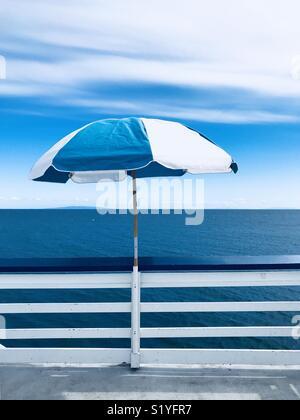 A blue and white umbrella at the end of the Malibu pier. Malibu, California USA. - Stock Image