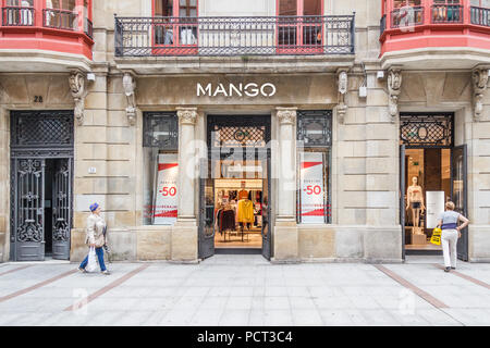 Gijon, Spain - 6th July 2018: Shoppers walking past Mango shop on Calle Corrida. This is one of the main shopping streets. - Stock Image