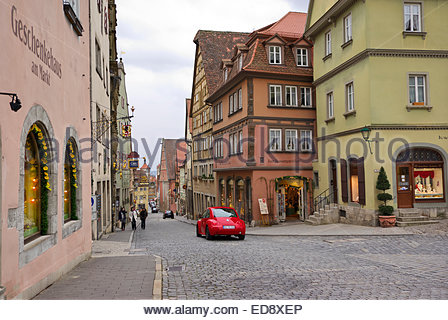 Tourists walk on Obere Schmiedgasse toward Marktplatz in Rothenburg ob der Tauber as a vivid red Volkswagen New - Stock Image