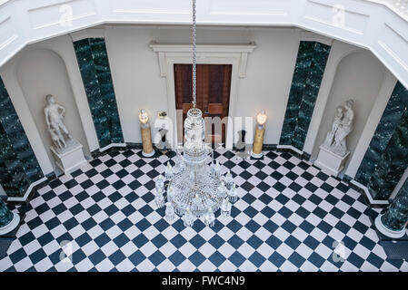 Crystal chandelier hanging over a black and white chequerboard tiled floor in a large entrance hall of a stately - Stock Image