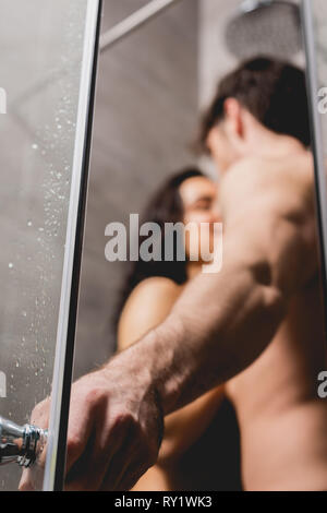 selective focus of man holding handle and hugging with woman in shower cabin - Stock Image