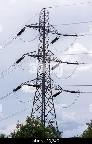 Electricity pylon against a background of a grey cloudy sky - Stock Image