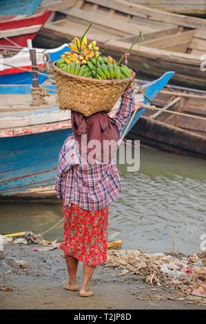 Woman carrying a basket of bananas on the banks of the Irrawaddy River, Mandalay Myanmar (Burma) - Stock Image