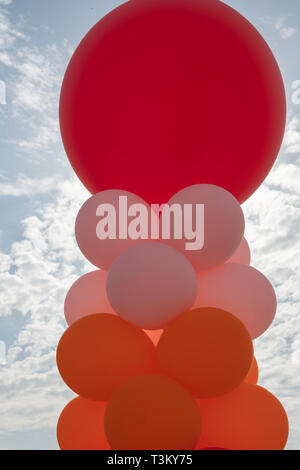 Red Giant Ballons against sun - Stock Image