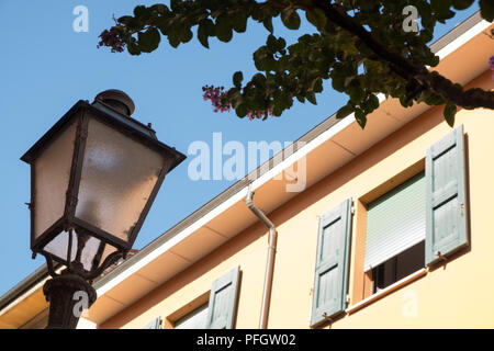 A street lantern in street with wooden window shutters, Castel San Pietro Terme, a small city and comune in the Metropolitan City of Bologna, Italy. - Stock Image