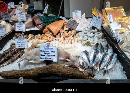 Shellseekers Fish and Game Ltd seafood stall at Borough Market, London in December, with food such as Black Cod fillets, swordfish loin, peeled prawns - Stock Image