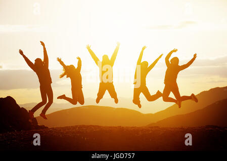 Happy friends jumping sunset mountains - Stock Image