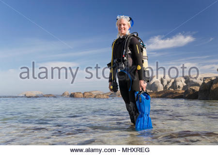 Woman in wetsuit going ocean scuba diving from beach and smiling at camera - Stock Image