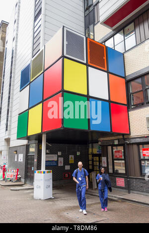 Doctors and a Rubik's cube type art installation outside Great Ormond Street Hospital in London, England, UK - Stock Image
