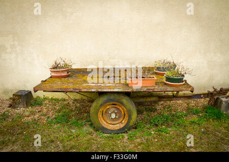 Trailer with flower pots sitting by a wall. - Stock Image