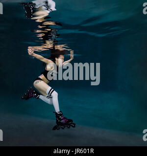 Young woman roller blading underwater, Virginia Beach, VA - Stock Image