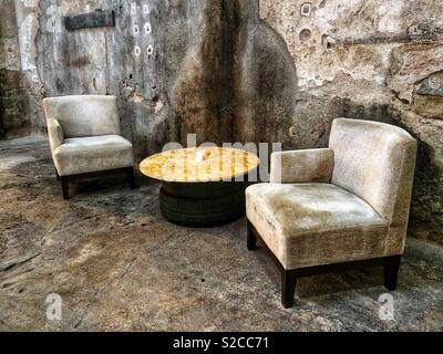 Two vintage armchairs in the hall of an old industrial building - Stock Image