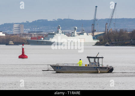 Glasgow, Scotland, UK. 28th Mar, 2019. Exercise Joint Warrior preparations on the River Clyde, Glasgow. The tiny Renfrew Ferry - a passenger ferry service linking the north and south banks of the River Clyde in Glasgow - makes a crossing after the giant Danish HDMS Absalon L16 passes by ahead of her participation alongside warships, submarines and aircraft from 13 other countries for the two-week exercise in Scotland between March 30 and April 11 Credit: Kay Roxby/Alamy Live News - Stock Image