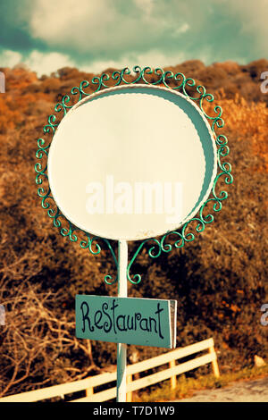White blank oval metal sign and a wooden rectangular restaurant signboard with forest and sky background - Stock Image