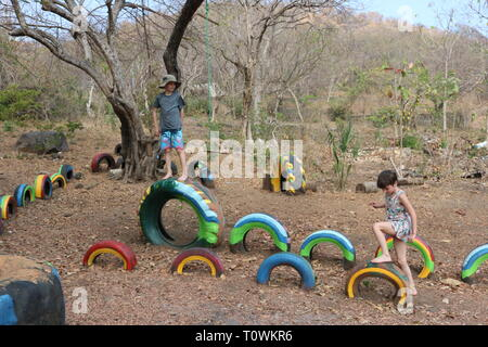 Children playing on a playground in Central America made of brightly painted recycled tires - Stock Image