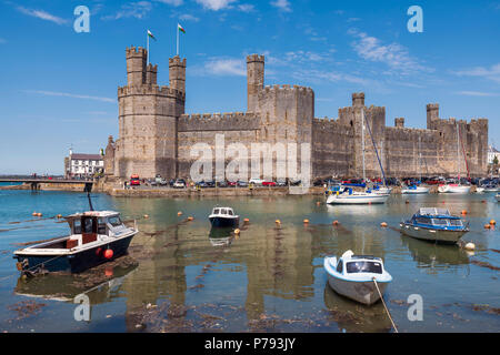 Caernarfon Castle Wales, UK. Sunny day in summer, with boats in the harbour. - Stock Image