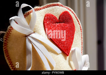 close up off small bag whith decorative red heart pregnancy annoucement concept. - Stock Image