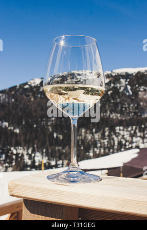 Picture of a glass of white sparkling Prosecco wine in a lodge in Cortina d'Ampezzo, Dolomites, Italy - Stock Image