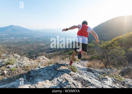A strong, atheletic man is seen from behind as he runs down full tilt on an arid, rocky trail in the mountains of El Arenal, Hidalgo, Mexico, as the s - Stock Image