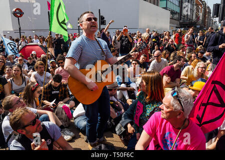 London, UK. 19th April 2019. A man plays and sings in the crowd at Extinction Rebellion's Sea of Protest after police surrounded the yacht at Oxford Circus. Police began a slow process of persuading protesters to leave by threatening them with arrest and cutting off those who were locked on around the bottom of the yacht. There were a number of arrests of protesters who refused to leave. A few tried to get the large crowd to protect the yacht, but XR organisers persuaded them not to physically oppose the police action. Peter Marshall/Alamy Live News - Stock Image