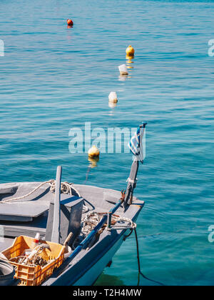 Traditional greek fishing boat with Greek Flag in Limenas Port, Thasos Island - Stock Image
