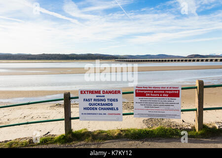 Quicksand and fast incoming tides danger warning signs at the River Kent estuary on the promenade at Arnside, Cumbria. - Stock Image