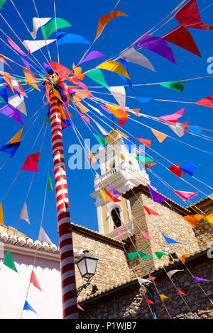 Sunlit bunting and a colourful pole against a church tower in a small Spanish village during fiesta. - Stock Image