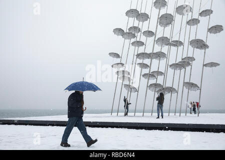 Thessaloniki, Greece. 09th Jan, 2019. A man walks past Umbrellas sculpture by George Zongolopoulos artist during a heavy snowfall in Thessaloniki, Greece on January 9, 2019.  Credit: Konstantinos Tsakalidis/Alamy Live News - Stock Image