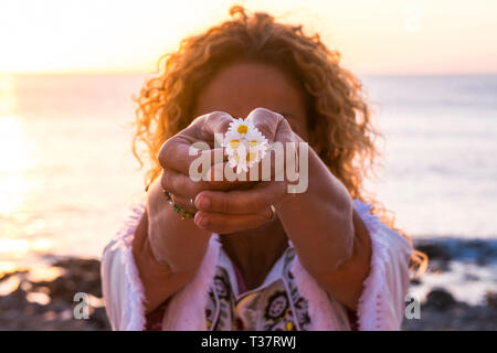 Environment and love for nature concept with curly blonde caucasian woman taking and showing a group of daisies with hands - sunset sunlight in backli - Stock Image