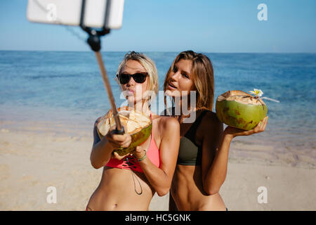 Two beautiful young women in bikini on the beach talking self portrait with smart phone on selfie stick. Female - Stock Image