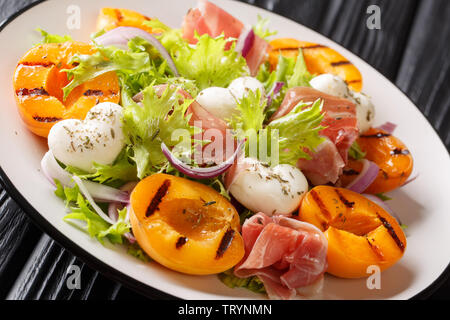 Easy dietary salad with mozzarella, prosciutto, grilled apricots, red onion and lettuce close-up on a plate on the table. horizontal - Stock Image