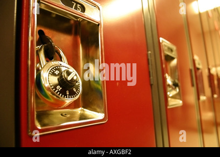 A length of red lockers sit silent and imposing with their locks shut. - Stock Image