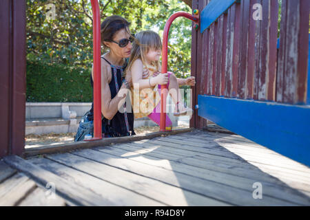 mother woman helping three years old blonde girl, with yellow dress and pink tights, to climb on wooden playground, in park of Madrid city - Stock Image