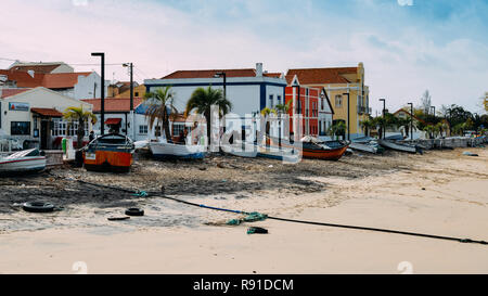 Trafaria, Portugal - Dec 16, 2018: Restaurants and bars along the seafront with wooden boats and pollutio at Trafaria, Portugal - Stock Image