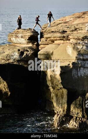 People exploring and jumping over rocky crevice on the sandstone cliffs of Sunset Cliffs, waves from Pacific Ocean, San Diego, CA, USA - Stock Image
