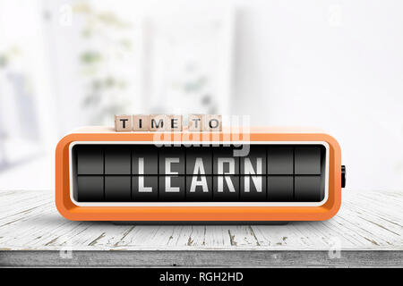 Time to learn message on a retro alarm clock in a bright room on a wooden desk - Stock Image