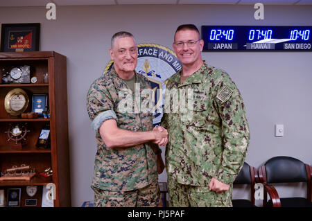 Maj. Gen. David Coffman, director, Expeditionary Warfare in the Office of the Chief of Naval Operations (OPNAV N95), left, shakes hands with Rear Adm. Dave Welch, commander, Naval Surface and Mine Warfighting Development Center (SMWDC), right, during a visit to SMWDC's headquarters. SMWDC is one of the Navy's five Warfighting Development Centers and its mission is to increase the lethality and tactical proficiency of the Surface Force across all domains. (U.S. Navy photo by Clinton Beaird/Released) - Stock Image