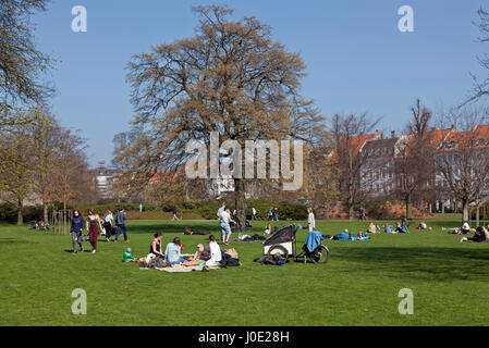 Young people enjoy the warm spring sun on Palm Sunday in Kongens Have, the King's garden, Copenhagen, Denmark. - Stock Image