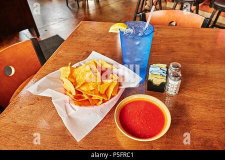 Chips and salsa or dip on a table top, shot from above, in a Mexican restaurant in Montgomery Alabama, USA. - Stock Image
