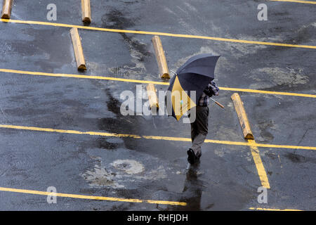 Man walking with umbrella in a parking lot, Condado, San Juan, Puerto Rico - Stock Image
