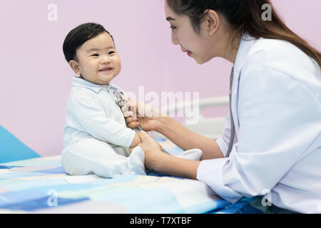 Asian doctor woman examining a little boy by stethoscope in hospital. Medicine and health care concept. - Stock Image