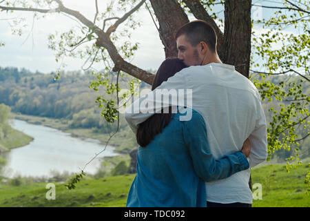 Couple of young beautiful man and woman hugging outdoors at sunny summer day at beautiful landscape background at countryside. - Stock Image