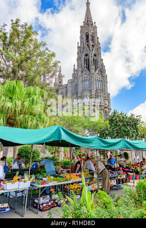 Fresh produce fruit and vegetables for sale in front of the gothic parish church tower of San Juan Bautista, Arucas Gran Canaria - Stock Image