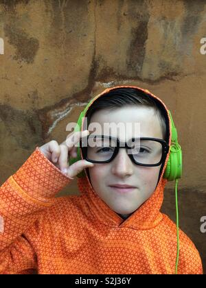 Young boy with black glasses listening to music on stereo headphones - Stock Image