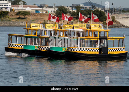 Tiny harbor taxi ferries perform a synchronized 'Ferry Boat Ballet' for crowds at the inner harbor during celebrations marking British Columbia Day August 4, 2018 in Victoria, BC, Canada. - Stock Image