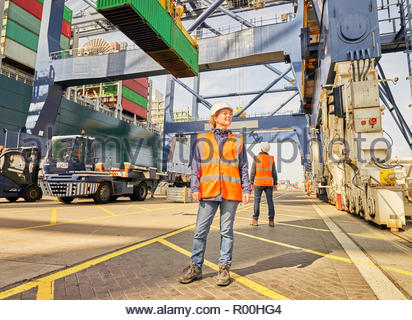 Dock worker in reflective vest beneath crane - Stock Image