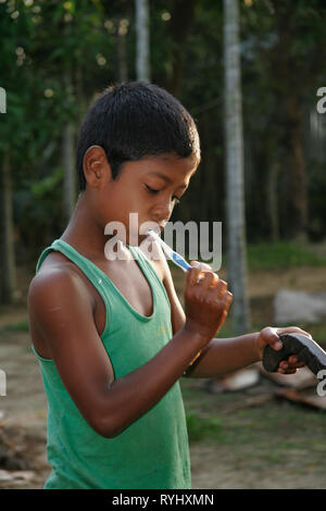 BANGLADESH Boy of  Garo tribal minority brushing his teeth, Haluaghat, Mymensingh region photo by Sean Sprague - Stock Image