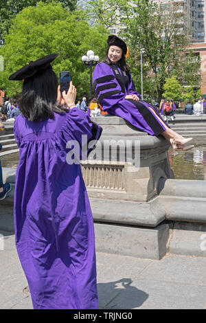 South Korean NYU graduates celebrate in Washington Square Park taking cell phone photos in their caps and gowns. New York City. - Stock Image